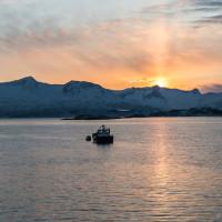 Boot im Sonnenuntergang vor den  Schneebedeckten Gipfeln in Troms